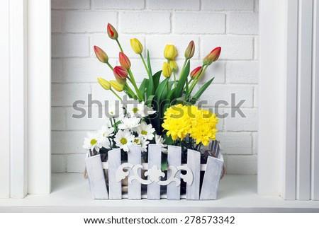 Beautiful flowers in ornamental flowerpot on wall background - stock photo