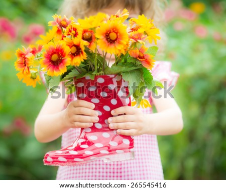 Beautiful flowers in red boots against spring background - stock photo