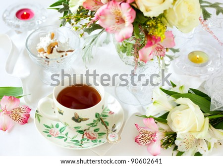 beautiful flowers in vase , cup of tea and biscuits - stock photo