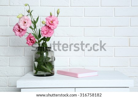 Beautiful flowers in vase on brick wall background - stock photo
