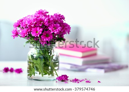 Beautiful flowers in vase on table in room