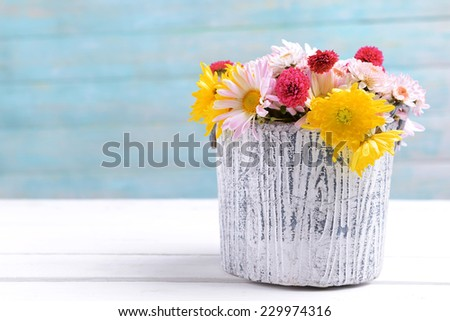 Beautiful flowers in vase on table on light blue background - stock photo