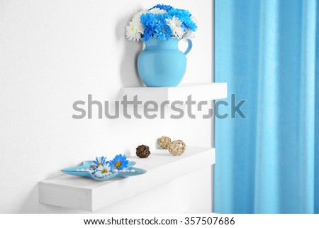 Beautiful flowers in vases and other decor on a shelves in room - stock photo