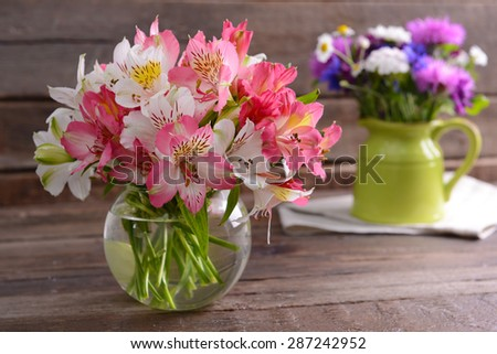 Beautiful flowers in vases on table close up - stock photo