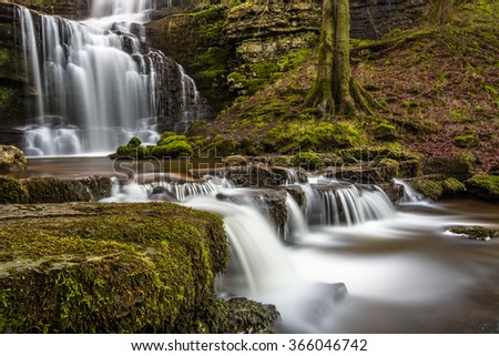 Beautiful flowing waterfall called Scaleber Force in North Yorkshire, UK. The waterfall is located in a peaceful countryside setting, surrounded by lovely forest/woodland environmental features. - stock photo