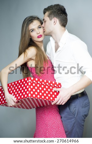 Beautiful fond young couple standing close to each other, holding big spotted red present box, vertical photo - stock photo