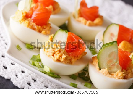 Beautiful food: Eggs stuffed with salmon and cucumber closeup on a plate. horizontal