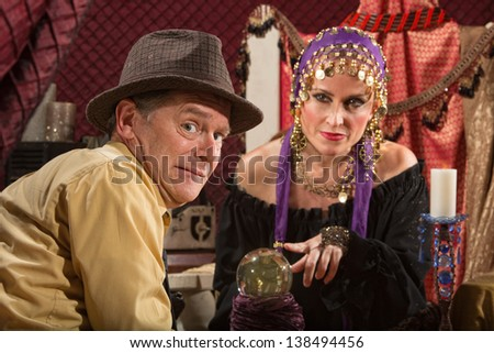 Beautiful fortune teller in head scarf and nervous male customer - stock photo
