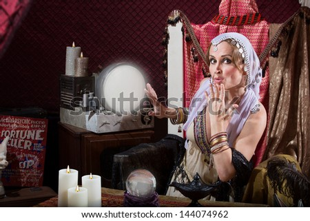 Beautiful fortune teller with hand over her mouth - stock photo