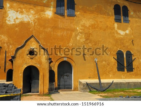 Beautiful fragment of ancient Galle Fort's wall with wooden door, storm window shutters and nautical anchor, Sri Lanka island, South Asia - stock photo