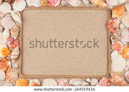 Beautiful frame made of rope with seashells on the sand, with a place for your creativity - stock photo