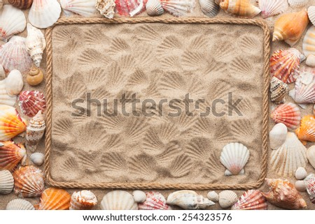 Beautiful frame of rope and sea shells on the sand, with place for your image, text - stock photo