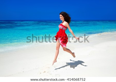 Beautiful free girl running on exotic beach with white sand and blue water. Happiness bliss freedom beach concept. Good life. Enjoyment. Summer Vacation. Nature background. - stock photo