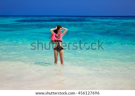 Beautiful free young woman in fashion swimsuit posing on the exotic sea, brunette summer portrait. Tropical beach. Enjoyment. Lifestyle. Freedom. Good life. Travel.  - stock photo