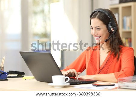 Beautiful freelancer female talking in a video conference on line with a headset with microphone and laptop in an office desktop or home desk - stock photo
