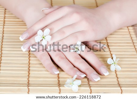 Beautiful french manicure with little flowers on a bamboo towel - stock photo