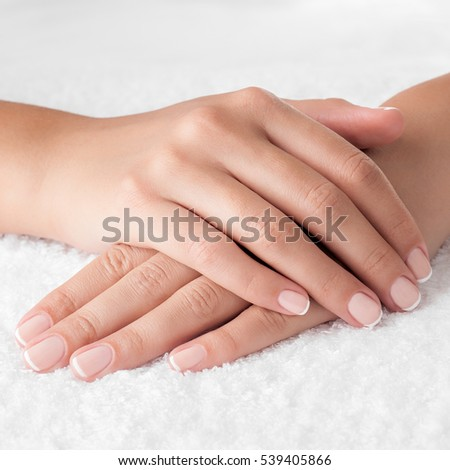 Beautiful french manicured woman hands on the white towel. Square composition.
