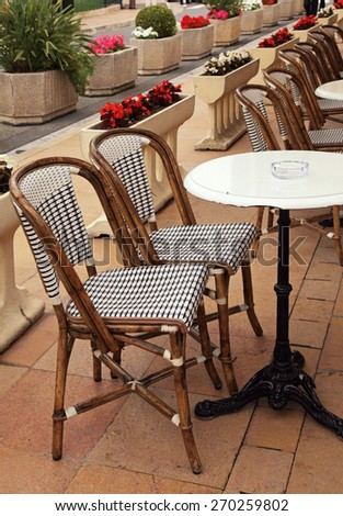 Beautiful french sidewalk cafe with small round tables and wicker chairs,Cote d'Azur,  Monaco. Vertical image, selective focus - stock photo