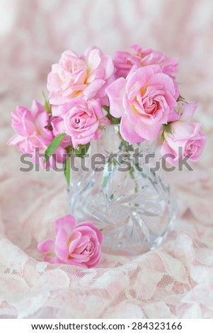 Beautiful fresh pink roses on a table .light background. - stock photo