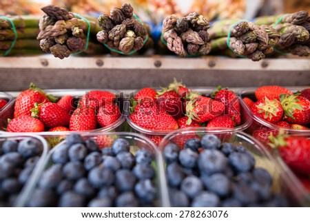 Beautiful fresh, ripe and delicious strawberries, blueberries and asparagus on a market stall - stock photo