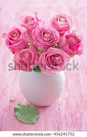 Beautiful fresh roses flowers in a vase on a pink background. - stock photo