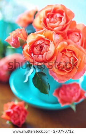 Beautiful fresh roses in a blue cup on a table. - stock photo