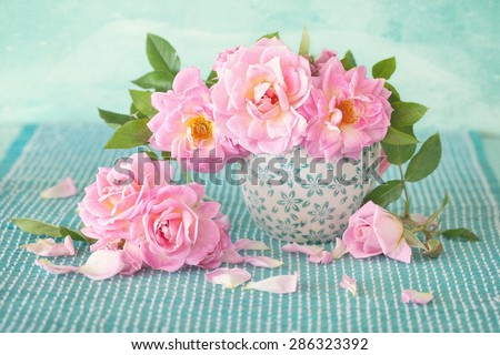 Beautiful fresh roses in a porcelain cup on a green background . - stock photo