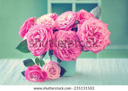 Beautiful fresh roses in a vase on a green background . - stock photo