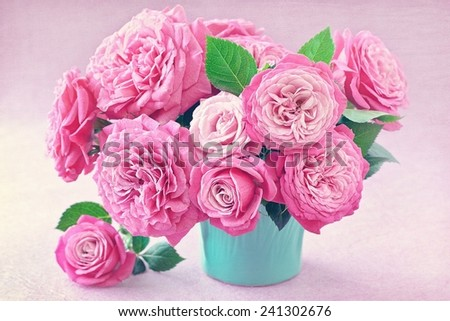 Beautiful fresh roses in a vase on a pink background. - stock photo