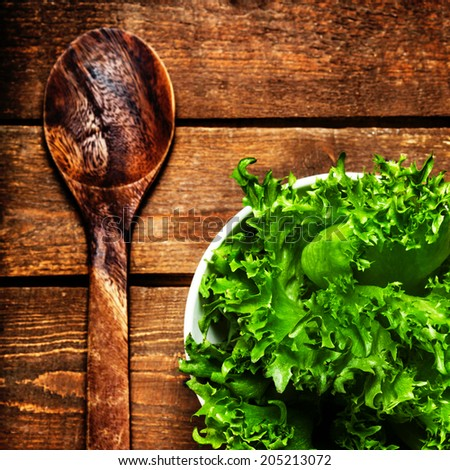 Beautiful Fresh Salad in a dish with wood spoon over vintage wooden table, top view, close up. - stock photo