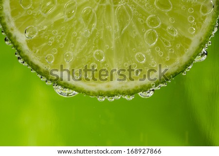 Beautiful fresh slice of lime in the water with bubbles - stock photo