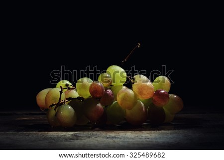 Beautiful fresh wet grapes on a wooden table on a black background. - stock photo