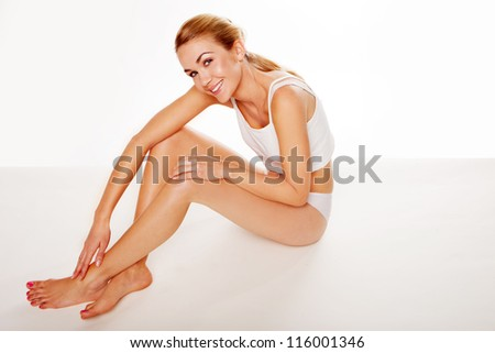 Beautiful fresh woman in lingerie with a lovely smile and long shapely legs sitting on the floor in a beauty and healthcare concept - stock photo