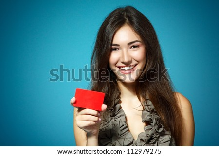 beautiful friendly smiling confident girl showing red card in hand, over blue background