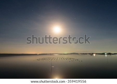 Beautiful full moon reflected on the calm water - stock photo