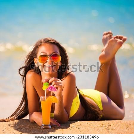 beautiful fun and joy brunette smiling lady woman in yellow bikini drink orange cocktail in  tropical  blue sea water bali has sports and tan body - stock photo