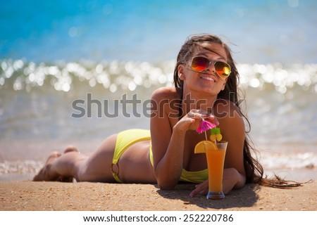 beautiful fun and joy brunette smiling  lady woman in yellow bikini drink orange cocktail in  tropical  blue sea water has sports and tan body - stock photo