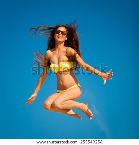 beautiful fun and joy brunette smiling woman in yellow bikini jump  blue sky  has sports and tan body - stock photo
