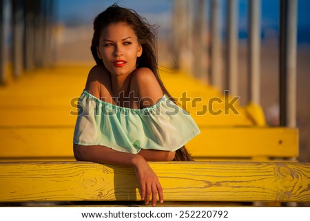 beautiful fun and joy brunette woman in blue blouse posing  yellow background has tan body and red smiling lips - stock photo