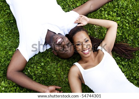 Beautiful fun happy smiling African American couple wearing white shirts laying in grass, faces of woman and man next to eachother in opposite direction.