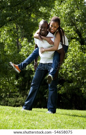 Beautiful fun happy smiling laughing African American couple piggyback playing in the park, woman hugging man, wearing white shirts and blue jeans. - stock photo