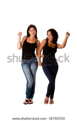 Beautiful fun happy smiling young women teenager girls dancing groovy, wearing black tank top and blue denim jeans, isolated. - stock photo