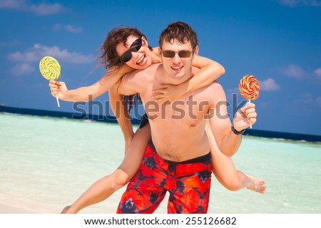 beautiful fun smiling sexy young women  and man with sweet candy lollipop in  romantic  atoll island paradise luxury  resort about coral reef, has sunglasses, honeymoon love - stock photo