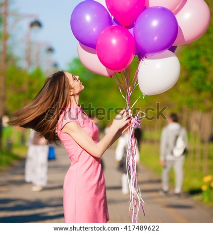 Beautiful fun woman holding multicolored helium balloons. Has smiling face, long hair, clothed pink dress, sunglasses. Has slim body. Portrait in city park. Sunny day and blue sky. Close up - stock photo