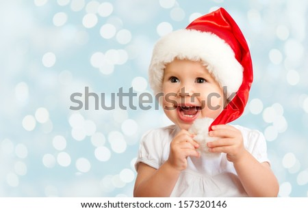 Beautiful funny baby in a Christmas hat  on blue background - stock photo