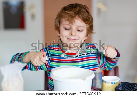Beautiful funny blond little kid boy baking cake and tasting dough in domestic kitchen. Happy child having fun with working with mixer, flour, eggs and fruits at home.