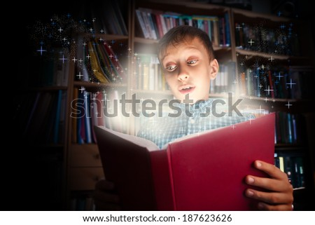 Beautiful funny child holding a big book with magical light looking amazed. Learning concept.  - stock photo