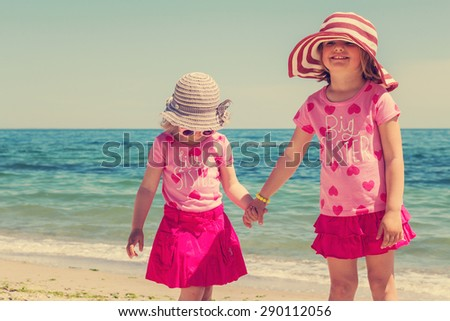 Beautiful funny little girls (sisters) in striped hats on the beach. The image is tinted.