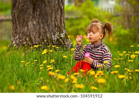 Beautiful funny lovely little five-year girl blowing soap bubbles in the park