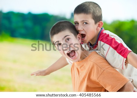 beautiful funny young smiling brothers play outdoor in countryside